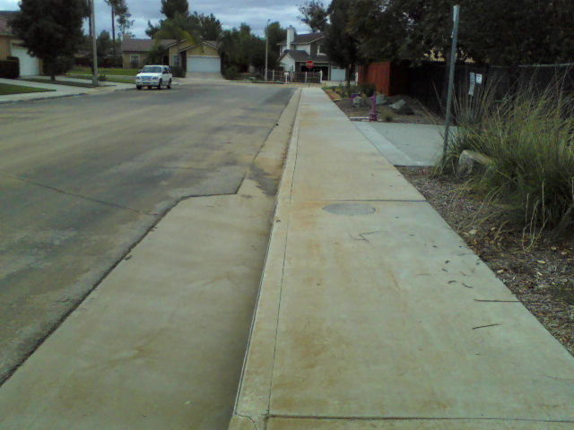 All the way to the corner dirt is covering the sidewalk