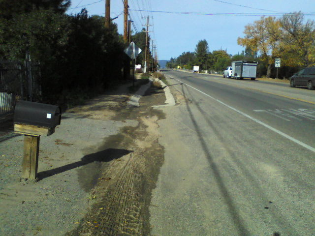 Standing at the end of the current roadside ditch before sheet flowing across Grand Avenue